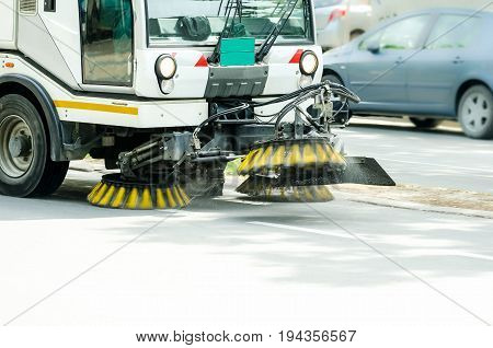 Street cleaner vehicle on the road. Vehicle sweeper with motion blur. Street cleaner vehicle sweeper.