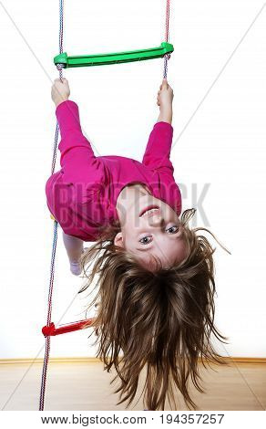 happy little girl climbing on a ladder at home