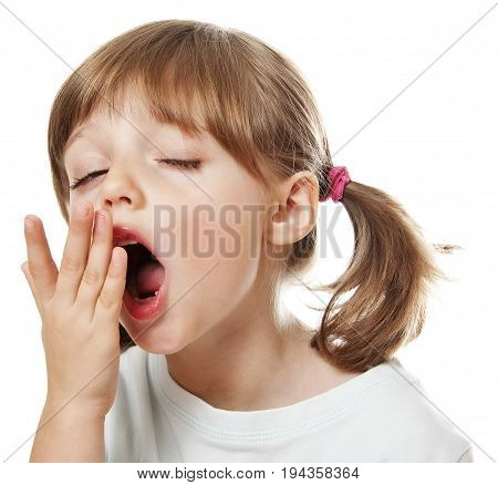 a tired little girl yawning - isolated