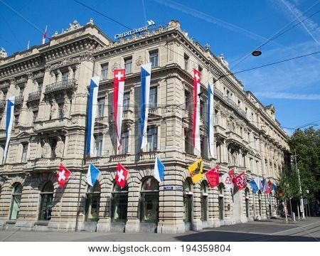 ZURICH - AUGUST 1: Swiss National Day parade on August 1, 2016 in Zurich, Switzerland. Facade of Credit Suisse building decorated with national flag and flags of cantons
