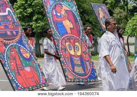 KOLKATA WEST BENGAL / INDIA - AUGUST 15TH 2016 : Folk dancers marching past in India's Independence day rally with artistic handicraft hoarding in their hands. The day in celebrtated all over India with joy.
