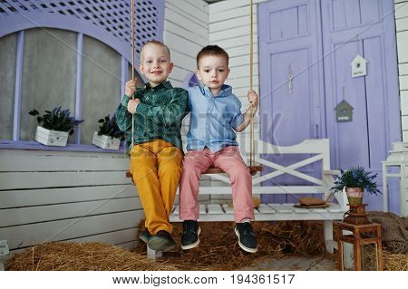 Two Little Boys Sitting On The Swin Outside The House With Straw On The Ground.