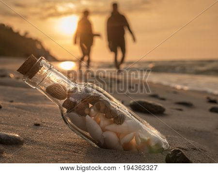 Corked bottle with seashells stuck in the sand on the beach against the sunset