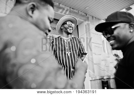 Black Men Stylishly Clothed Standing And Talking Outside On The Street In The Downtown.black And Whi