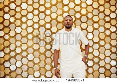 Attractive Mature African American Man In Stylish Clothing Posing Next To The Golden Wall.