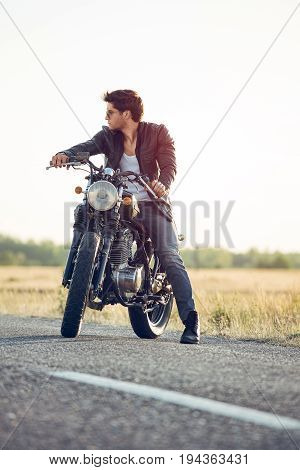 Motorcyclist with a cafe-racer motorcycle outdoors picture