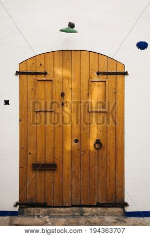 Front view on old fashioned wooden door with white wall in old town.