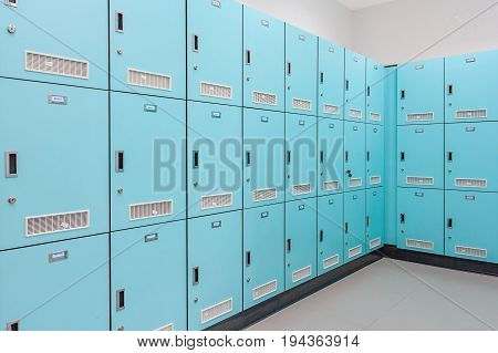 Stack of green metal school lockers with combination locks and doors shut as background