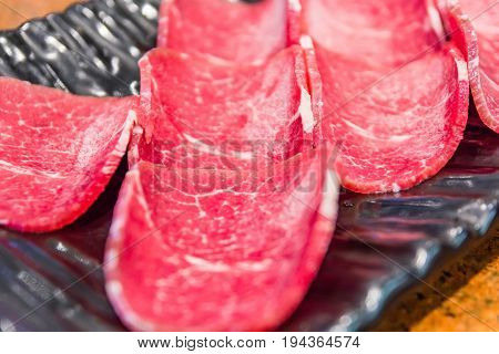 Raw pork sliced pieces on black plate with japanese sauce Prepared for Japanese Barbecue Style called Yakiniku Selective focus