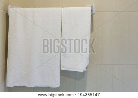 Bathroom Towel - white towel hanging on towel bar in bathroom for prepared to use