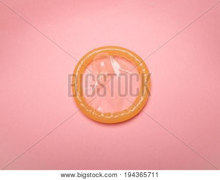pink condom isolated on pink background photo hiv prevention concept