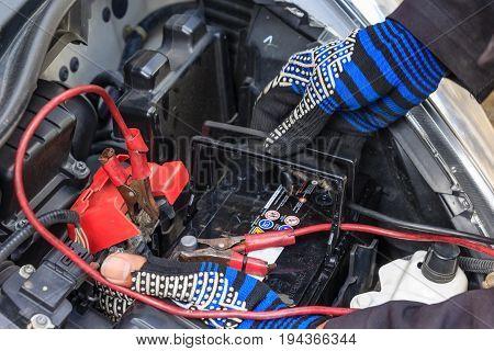 A car mechanic replaces a battery selective focus