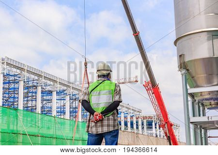 Supervisor holding walkie-talkie at construction site against clear sky