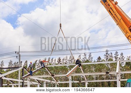 Worker working on steel and iron roof structure of under construction site building