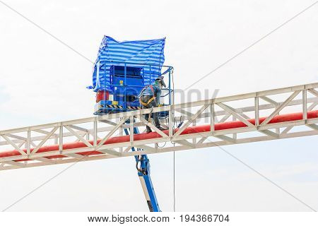 Workers welding steel structure on a high risk in factory building construction area
