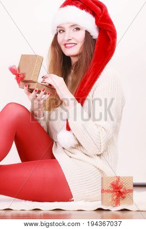 Cheerful woman wearing santa claus hat opening golden gift box with jewel pearls. Christmas time giving and happiness concept.
