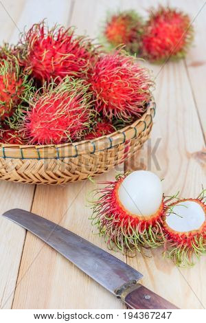 fresh tropical rambutan fruits over basket with knife on wood background fruit in Thailand