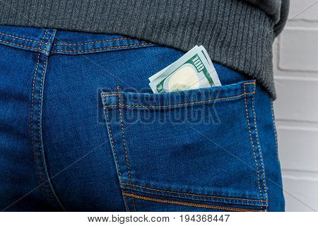 Dollars in the back pocket of men's jeans close-up