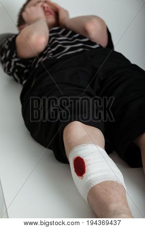 Crying Boy Laying Down With Injured Leg