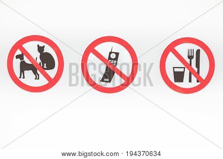 On this wall there are three prohibitions of no pets no cellphone and no food or drink