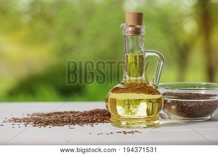 flax seeds and linseed oil in a glass jug on a wooden table