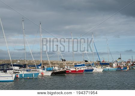 Pleasure yachts in a marina on a clouded sky