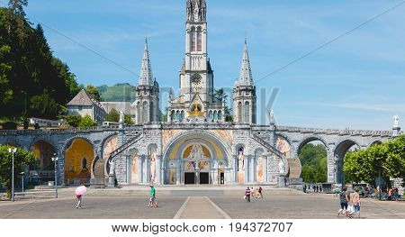 Tourists Walking In Front Of The Cathedral Of The Sanctuary Of Lourdes