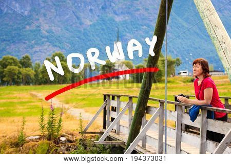 Tourism vacation and travel. Woman tourist relaxing on bridge looking at mountains landscape in norwegian village Oppstryn Sogn og Fjordane county. Norway Scandinavia. poster
