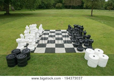 Outdoors giant chessboard on a grass field in a park