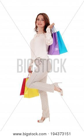 A young beautiful woman in a lace blouse and beige trousers holding some shopping bags standing in one leg isolated for white background.