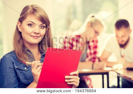 Education high school teamwork and people concept - smiling student girl with notebook sitting in front of students her group mates in classroom