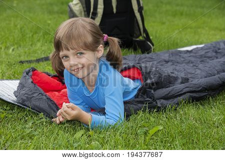 little girl camping with a sleeping bag