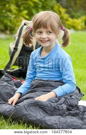 portrait of a little girl resting in a sleaping bag - camping concept
