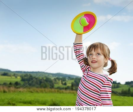 happy little girl playin with a ball in the park
