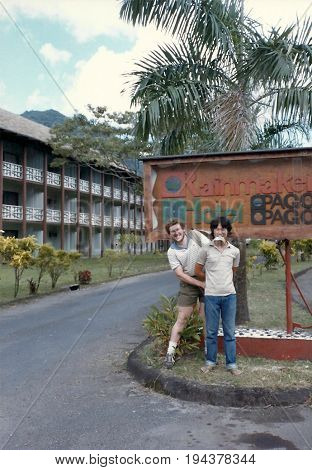 PAGO PAGO / AMERICAN SAMOA, CIRCA 1990: Two American tourists pose for a photograph in front of the famous Rainmaker Hotel.