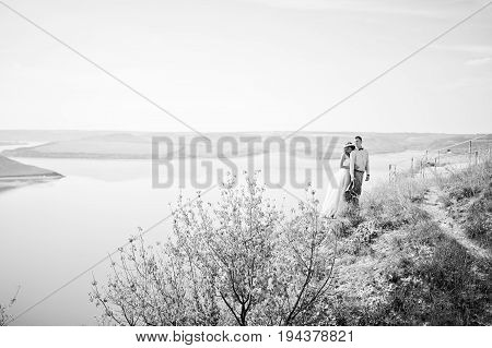 Fantastic Wedding Couple Standing On The Edge Of Rocky Precipice With A Perfect View Of Lake On The