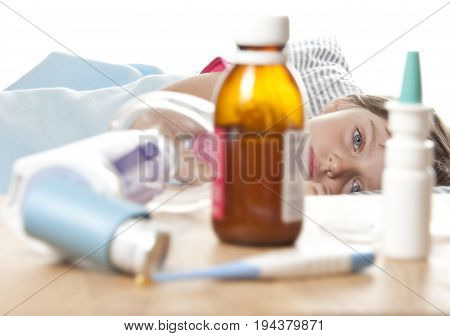 ill little girl and her drugs inhaler and thermometer