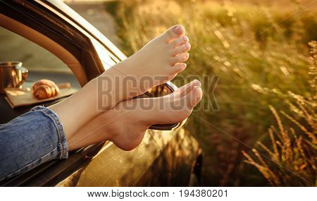 Woman legs out the windows in car . Conceptual freedom, travel and holidays image with copy space.