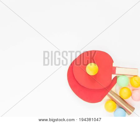 Sport background. Red ping-pong rackets and varicolored balls. Flat lay top view