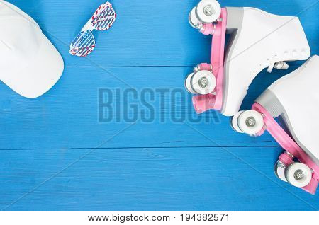 Sport, healthy lifestyle, roller skating background. White roller skates, sunglasses, white baseball cap. Flat lay, top view.