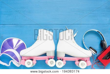 Sport, healthy lifestyle, roller skating background. White roller skates, retro headphones and pink visor hat. Flat lay, top view.