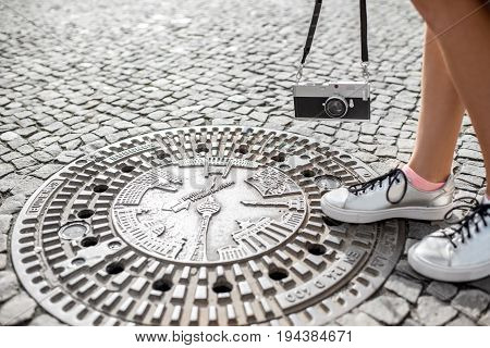 View on the branded manhole sewer with woman legs and photocamera in Berlin