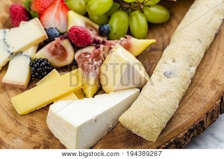 Cheese plate with bread grapes and strawberries in a wooden desk on marble surface.