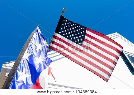 American flags with backround of typical house New England