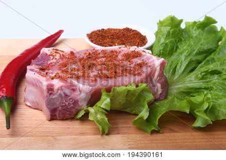Raw pork chops with herbs and spices on cutting board. Ready for cooking