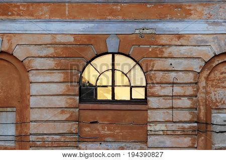 The light from the sun is reflected in the semicircular window of the historic house during sunset