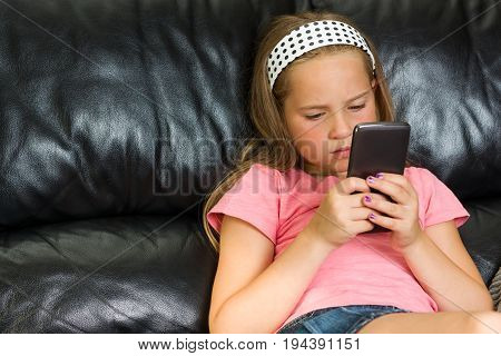 Pretty little girl with smartphone on the couch