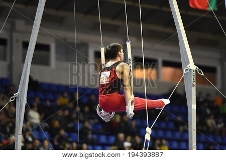 Kyiv. Ukraine-April 1, 2017 : Male gymnast performing on stationary gymnasic rings during Stella Zakharova Artistic Gymnastics Cup