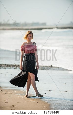 Sexy young woman in long black skirt strolling along the beach surf line.
