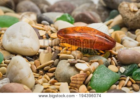 Amber stone. Mineral amber. Rosin yellow amber. Sunstone on a beach of pebbles background.